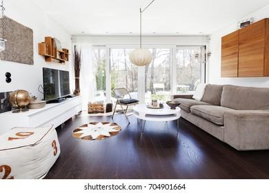 home interior living room with dark wooden floor, sofa and Tv  big windows