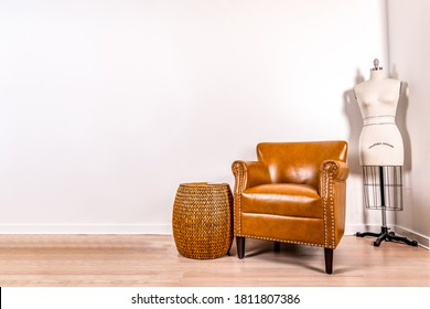 Home interior mock up. A cute leather chair with a bamboo end table and a vintage dress form against a white wall.