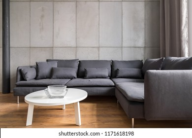 Home interior with modern concrete wall, big corner sofa and white table