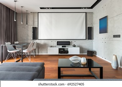 Home interior with projector screen, table, chairs and cabinet