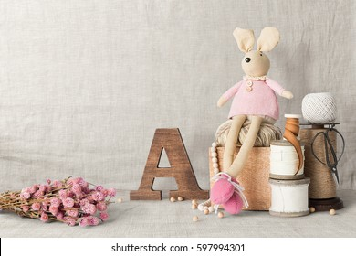 Home interior table scene, front view, with decor elements, flowers, toys and blank copy, logo space on fabric background.