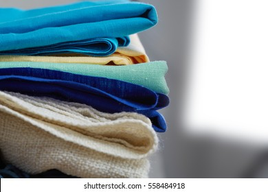 Home interior, tailor, sewing, diy concept. Heap of colorful cloth fabrics. Color Wool, cotton linen clothes. Closeup.