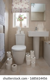 A home interior of a tiled bathroom with white suite and the toilet covered in toilet rolls after panic buying during the Coronavirus Pandemic