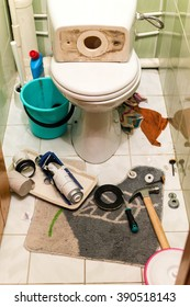 Home interior toilet repairs shows work in progress. Plumbers tools displayed around the components of the toilets flush system including a float device and gaskets. White porcelain toilet