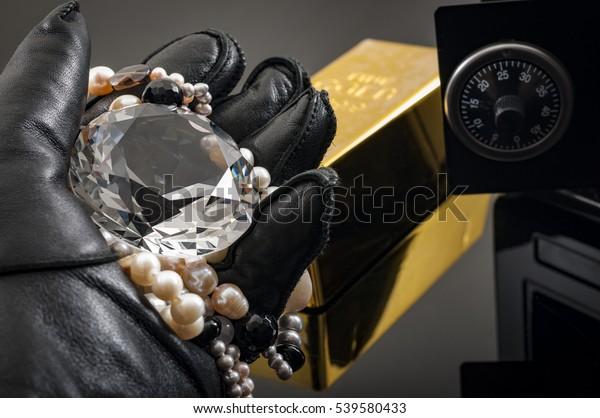 Invasión doméstica y concepto de robo con la mano en guantes de cuero sosteniendo un collar de diamante y perla