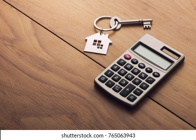 Home key chain and calculator on wooden surface