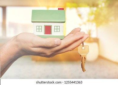 Home key in house keychain on woman/ man/ human hand support offering security protection awareness concept: Insurance agent in white shirt holding happy residential key lock/ unlock insure habitat