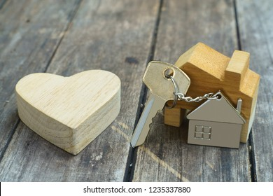 Home key with house keychain and wooden heart mock up on vintage wood background, home sweet home concept