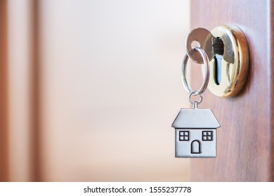 home key with house keyring in the door keyhole. Buy new home concept