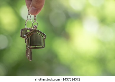 Home key with house keyring hanging with green garden background, copy space