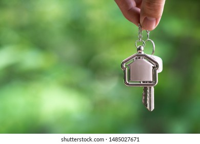 Home key with house keyring hanging with white wall background, copy space