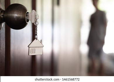 Home key with house keyring in keyhole on wooden door, copy space
