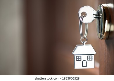 Home key with house keyring in keyhole on wooden door close up