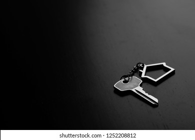 Home key with house keyring on black wood table in dark tone, copy space, real estate concept
