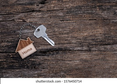 Home key with house keyring on rustic wood background, copy space