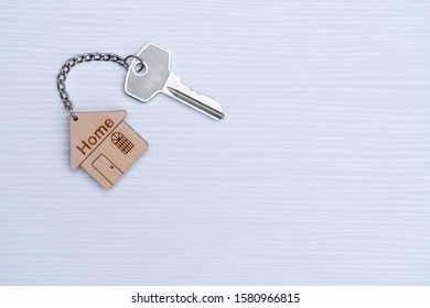 Home key with house keyring on white background, copy space