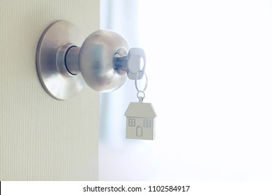 Home key with metal house keychain in keyhole, property concept