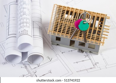 Home keys, small house under construction and rolls of diagrams on electrical drawings for project, concept of building home