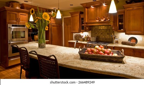 Home Kitchen with Island, Sink, Cabinets, Pendant Lights, Oven, Stove-top Range, and Hardwood Floors in New Luxury House
