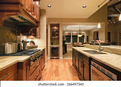 Home Kitchen with Island, Sink, Cabinets, Pendant Lights, Stove-top Range, and Hardwood Floors in New Luxury House
