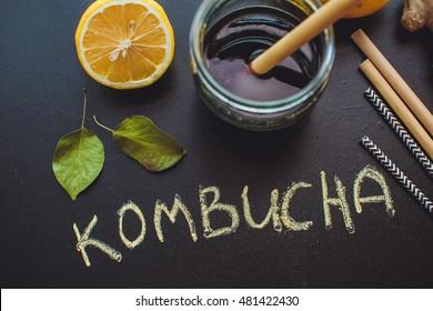 Home Kombucha with lemon and apple on slate with leaves