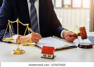 Home and land lawsuit concept, Lawyers hold a gavel to judge law and land to client.
