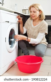 Home laundry. Happy mature woman using washing machine at home