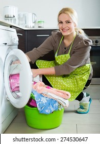 Home laundry. Smiling american  girl using washing machine at home