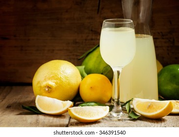 Home lemon liquor, lemon liqueur in a glass and fresh lemons and limes on the old wooden background in rustic style, selective focus