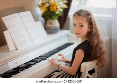 Home lesson on music for the girl on the piano. The idea of activities for the child at home during quarantine. Music concept