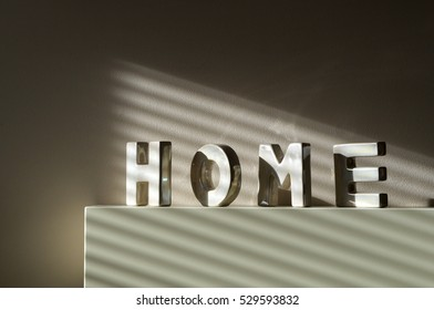 Home letters words oranments on fireplace with window shadow