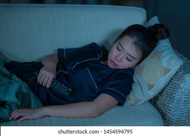 home lifestyle portrait of young beautiful and tired Asian Korean woman in pajamas holding TV remote falling asleep on living room sofa couch while watching television show or movie at night