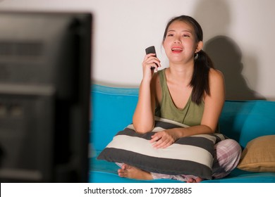 home lifestyle portrait of young happy and beautiful Asian Chinese woman watching TV  at living room sofa couch enjoying funny television Korean drama show or comedy movie relaxed and cozy