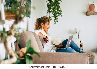 Home lifestyle real scene with people and technology .- beautiful woman sit down on the sofa and use laptop computer and connection for work or look for the web - female caucasian and smart working