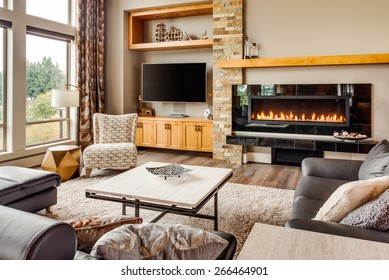 Home living room with hardwood floors, fireplace with roaring fire, coffee table, and mantle in new luxury house