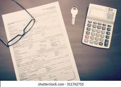 Home loan application form on desk with glasses, key and calculator, viewed from above