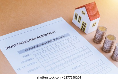Home loan and Business investment concept. Closeup application form of Mortgage loans, pen, key, calculator and  model wooden house with coins stack.