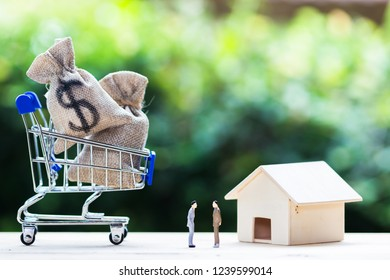 Home loan, mortgages, debt, savings money for home buying concept : US dollar money bag in shopping cart, residential, house on table against green nature background. Exchange of finances and houses.