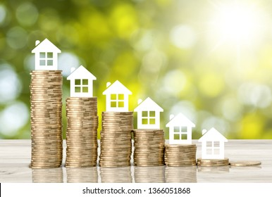 Home loan / reverse mortgage, asset refinancing concept : Small house or home on stacks of coins, depicts a homeowner or a borrower turns properties into cash, saving money to buy shelter, basic need