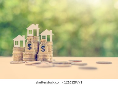Home loan / reverse mortgage and saving for a real estate concept : House model, US dollar money bag on coins, depicts saving for a house or flat manageable and turn a home buying dream into reality