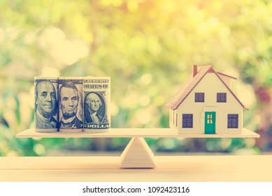 Home loan / reverse mortgage or turning assets or real estate into cash concept : House model, US dollar bank notes on a simple balance scale, depicts homeowner or borrower turns properties into cash
