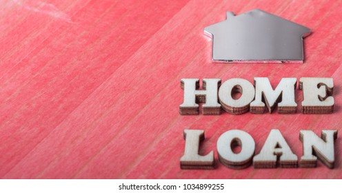 'Home Loan' text with metal shape house symbol over red wooden table top. Conceptual image.