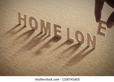 HOME LONE wood word on compressed or corkboard with human's finger at E letter.