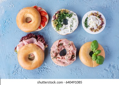 Home made American bagels with ham and olives decorated with herbs, greek olives, tomatoes and cheese. Top view.