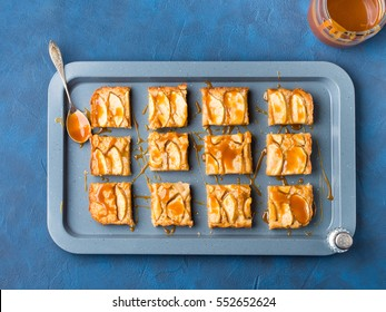 Home made apple cinnamon blondies with salted caramel. Sweet food home made dessert treat. Dark blue background flat lay