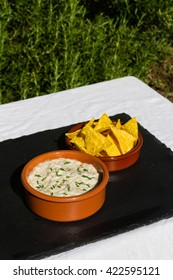 Home made aubergine dip in orange ceramic bowl and tortilla chips on the side. On slate mat, outside on linen covered table.