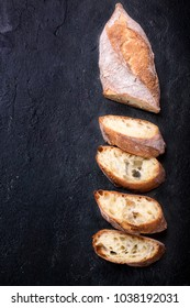 Home made baguette rustic cut in slices over a black stone background. Top View. Rustic bread concept