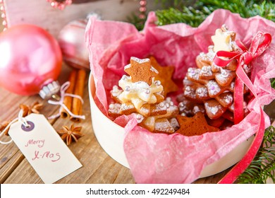 Home made baked Christmas gingerbread tree as a gift for family and friends. Christmas decoration in pink. With icing sugar as snow. Selfmade gift