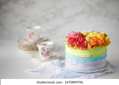 home made beautiful cake for Birthday,Valentine,Festive, Wedding cake buttercream decorate roses pastel color in white dish with cup of tea on blue cloth and white background closeup copy space