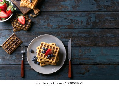 Home made Belgian waffles served with berries over a rustic wooden background. Top view. Copy space